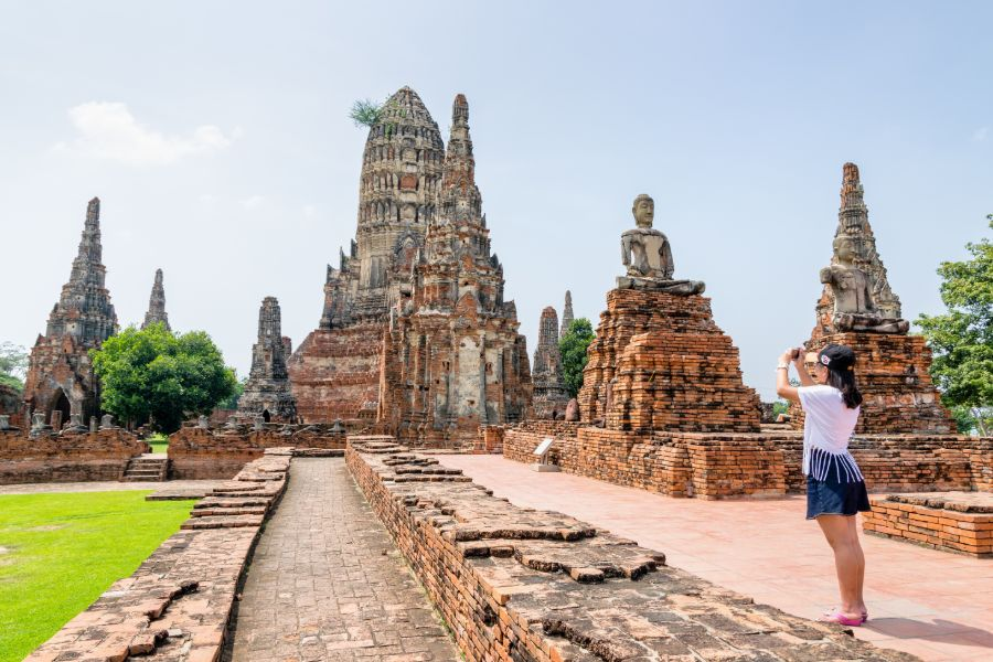 Thailand Ayutthaya Historical Park pagoda of Wat Chaiwatthanaram Buddhist temple famous tourist attraction Tourist takes a photo