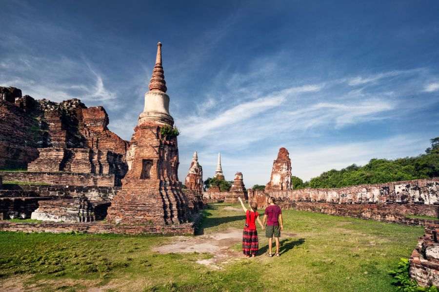 Thailand Ayutthaya Wat Mahathat boedhistische tempel Young couple with photocamera looking at ancient ruined tempel