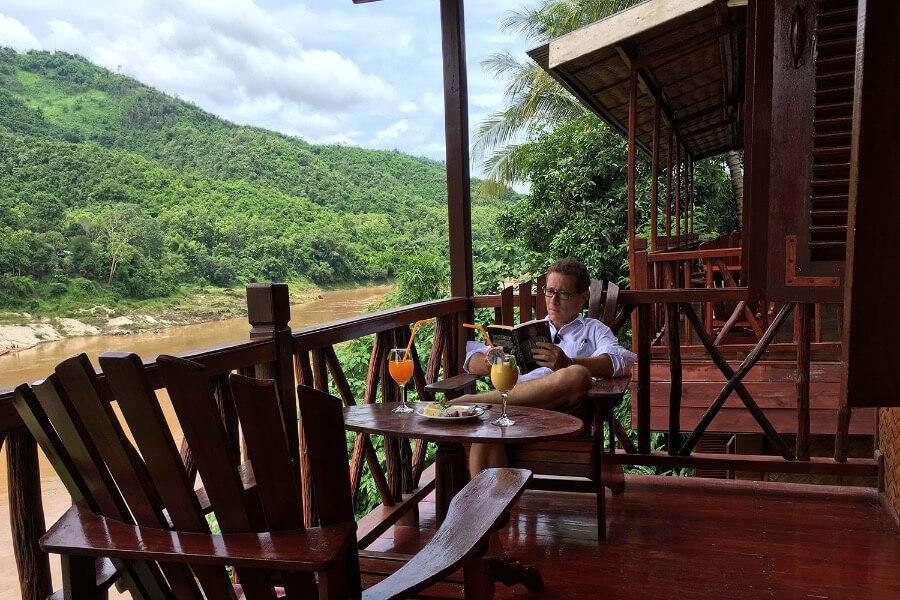 Laos Luang Prabang Shompoo Cruise Houay Xay toerist leest boek en drinkt uitzicht genieten